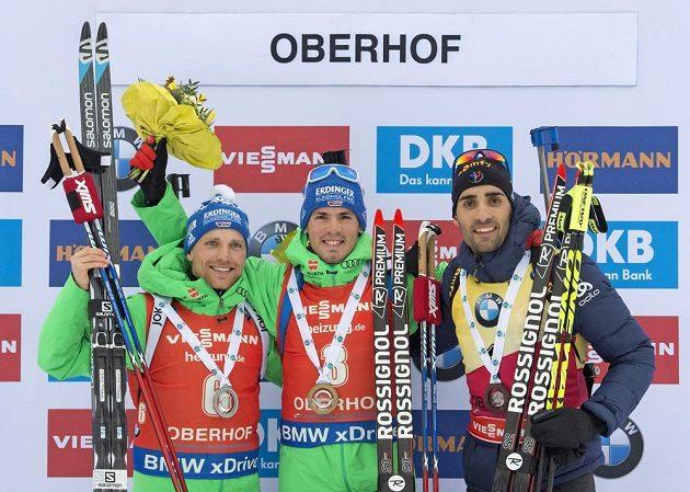 Simon Schempp oslavuje na bedně své vítězství s druhým Erikem Lesserem a třetím Martinem Fourcadem.