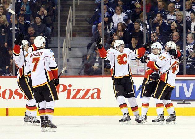 Jiří Hudler (druhý zprava) se raduje z vítězství Flames na ledě Winnipegu.