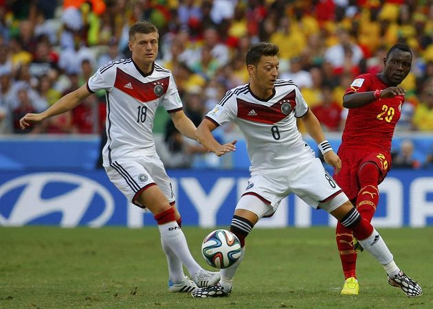 Ghaňan Asamoah (vpravo) bojuje o míč s Němci Mesutem Özilem (uprostřed) a Tonim Kroosem.