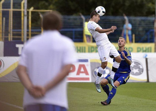 Plzeňský Jan Kovařík hlavičkuje míč pryč před dotírajícím Lukášem Kryštůfkem (vpravo) z Jihlavy.