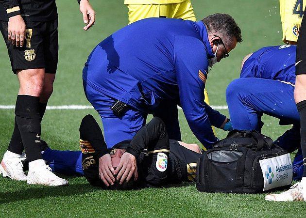 Barcelonský špílmachr Lionel Messi je ošetřován po ošklivém zákroku jednoho ze soupeřů v ligovém utkání s Villarrealem.