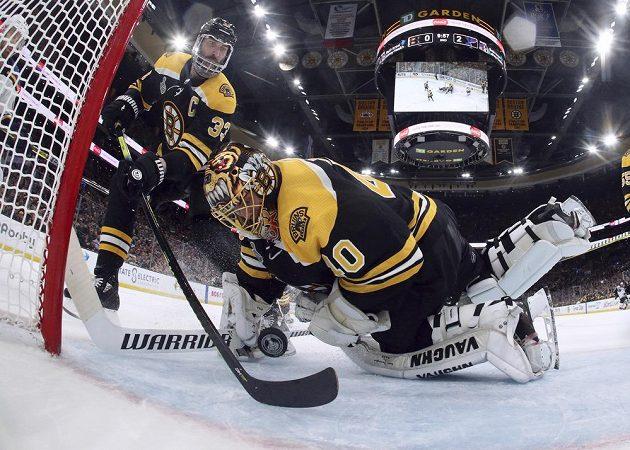 Brankář Bostonu Tuukka Rask se za asistence kapitána týmu Zdena Cháry snaží zkrotit puk v rozhodujícím sedmém finále Stenley Cupu proti St. Louis.