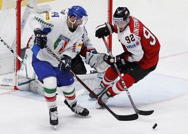Rakouský hokejista Clemens Unterweger a Ital Angelo Miceli v akci během utkání mistrovství světa.