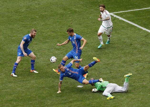 Maďarský brankář Gábor Király (v zeleném dresu) chyboval, neudržel centr a po následném závaru byl nařízen pokutový kop pro Islanďany. Přes gólmana padá Ragnar Sigurdsson (6).
