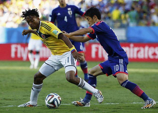 Kolumbisjký záložník Juan Cuadrado (vlevo) bojuje o míč s Japoncem Šindžim Kagawou.
