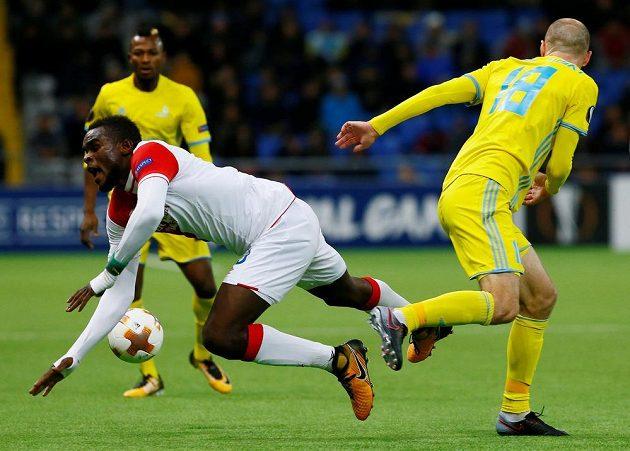 Fotbalista Slavie Michael Ngadeu-Ngadjui padá k zemi po souboji s Ivanem Majevským z Astany v utkání Evropské ligy.