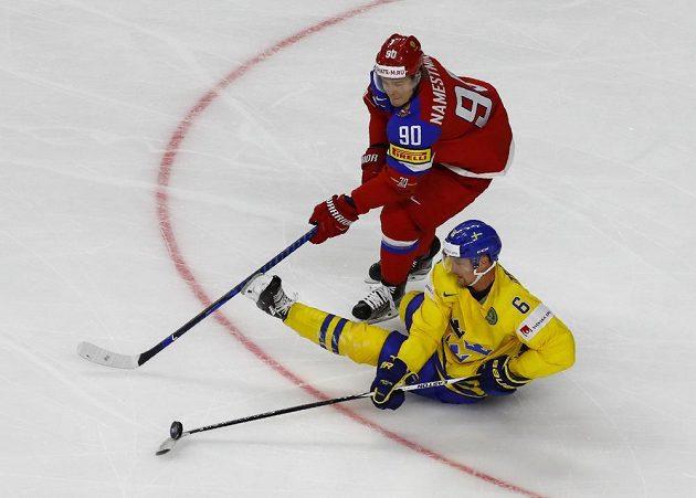 Hokejové mistrovství světa 2017 začalo soubojem Švédska s Ruskem. Švéd Anton Stralman v pádu odehrává puk před Vladislavem Namestnikovem z Ruska.