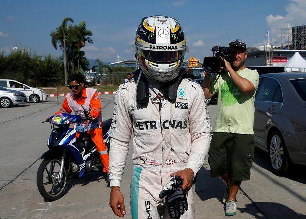 Zklamaný Lewis Hamilton opouští závod poté, co mu vzplál motor.