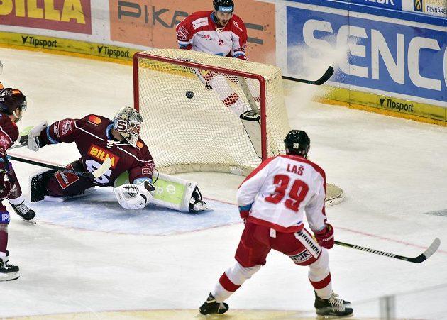 Olomoucký hokejista Marek Laš střílí gól brankáři Sparty Davidovi Honzíkovi.
