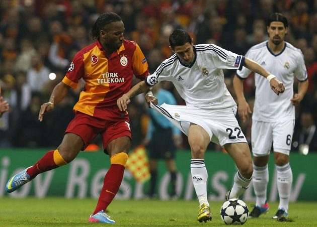 Útočník Galatasaraye Didier Drogba (vlevo) a Angel Di María z Realu Madrid bojují o míč.