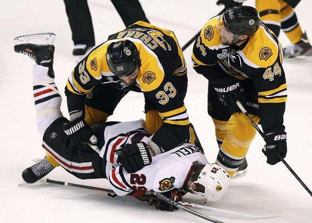 Obránce Bostonu Zdeno Chára (s číslem 33) posílá na led útočníka Chicaga Bryana Bickella. Vpravo přihlíží zadák Bruins Dennis Seidenberg.