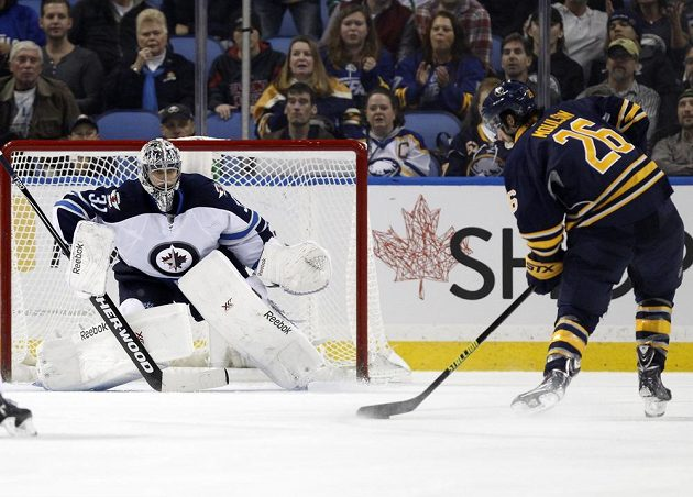 Ondřej Pavelec (31) z Winnipegu v utkání s Buffalem, ohrozit se ho snaží Matt Moulson (26.