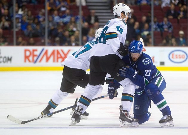 Tomáš Hertl (uprostřed) v souboji s hvězdou Vancouveru Danielem Sedinem.