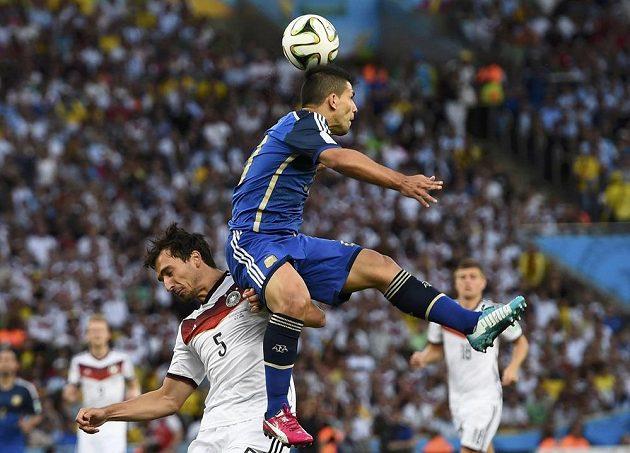 Argentinský útočník Sergio Agüero (ve výskoku) v souboji s německým stoperem Matsem Hummelsem.