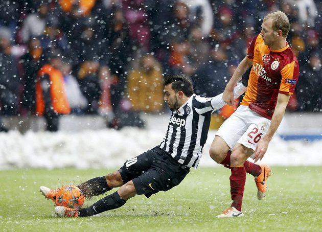 Semih Kaya z Galatasaraye (vpravo) v souboji s Carlosem Tévezem z Juventusu.