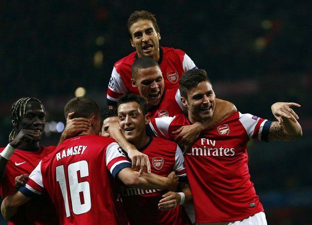 Fotbalisté Arsenalu oslavují úvodní trefu Mesuta Özila (dole uprostřed) v utkání Ligy mistrů proti Neapoli.