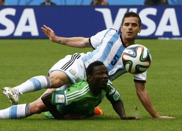Argentinec Fernando Gago (nahoře) v souboji s Juwonem Oshaniwou z Nigérie.