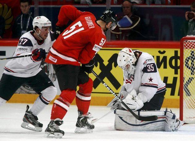 Švýcarský útočník Ryan Gardner (uprostřed) se snaží překonat amerického brankáře Johna Gibsona. Vlevo přihlíží obránce USA Justin Faulk.