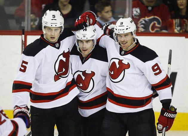 Adam Henrique (uprostřed) z New Jersey oslavuje trefu na ledě Calgary i s českým útočníkem Martinem Havlátem (vpravo).
