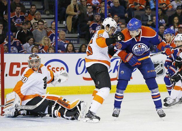 Brankář Flyers Michal Neuvirth se otáčí za střelou Leona Draisaitla (29) z Edmontonu.