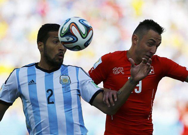 Argentinský obránce Ezequiel Garay (vlevo) v souboji se švýcarským útočníkem Josipem Drmičem.