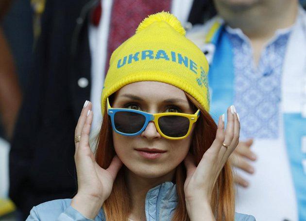 Fanynka Ukrajiny sleduje v brýlích zápas s Německem.