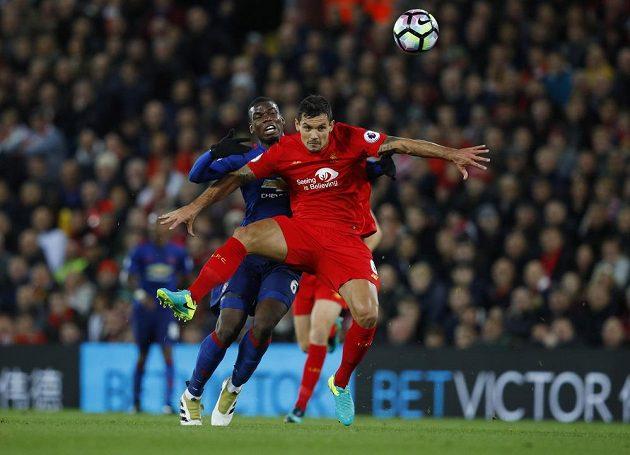 Stoper Liverpoolu Dejan Lovren hlavičkuje míč před Paulem Pogbou z Manchesteru United.