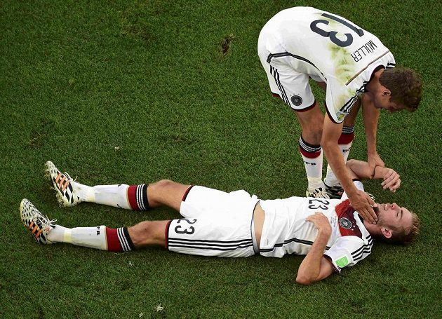 Thomas Müller se sklání nad otřeseným Christophem Kramerem.