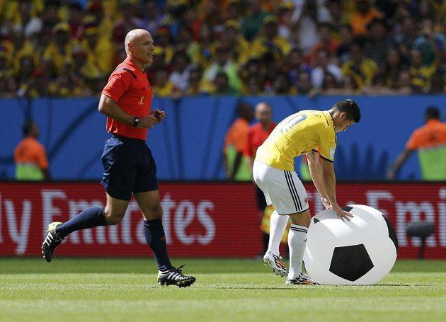 Rozhodčí Howard Webb a Kolumbijec James Rodriguez s nezvyklou překážkou ve hře.