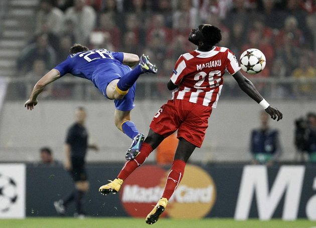 Stephan Lichtsteiner (vlevo) z Juventusu ve vzdušném souboji s Arthurem Masuakuem z Olympiakosu v utkání Ligy mistrů.