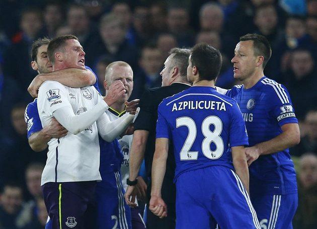 Branislav Ivanovič z Chelsea (vlevo) drží pod krkem Jamese McCarthyho z Evertonu. Všemu přihlíží rozhodčí Jonathan Moss.