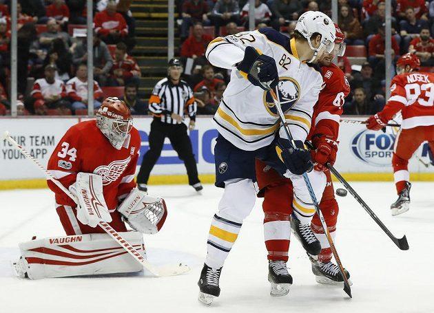Český gólman Detroitu Petr Mrázek v brance Rudých křídel v duelu NHL s Buffalem Sabres. Před brankou mu cloní Marcus Foligno z Buffala, hlídá jej Xavier Ouellet. Detroit zápas prohrál 1:2.