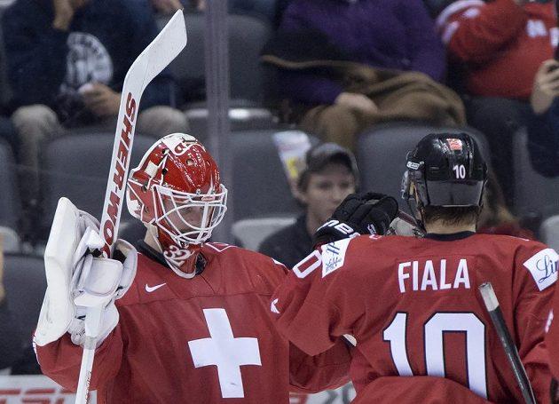 Švýcarský brankář Gauthier Descloux (vlevo) se raduje se spoluhráčem Kevinem Fialou z vítězství nad Českem.