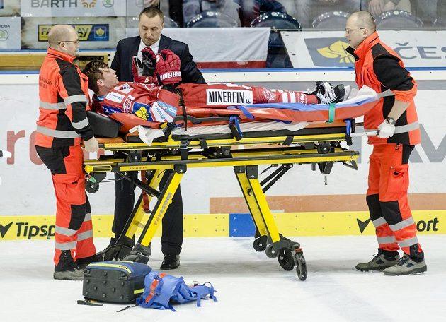 Zraněný Daniel Rákos z Třince opouští ledovou plochu v Pardubicích na nosítkách.