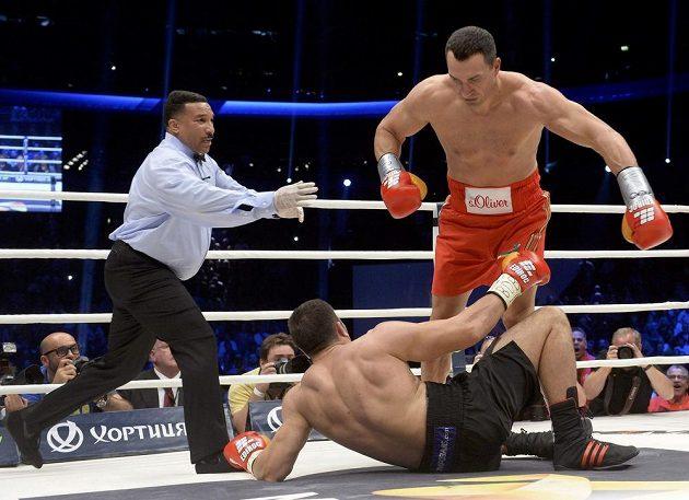 Ukrajinský boxerský šampión Vladimir Kličko sráží k zemi bulharského vyzyvatele Kubrata Puleva.