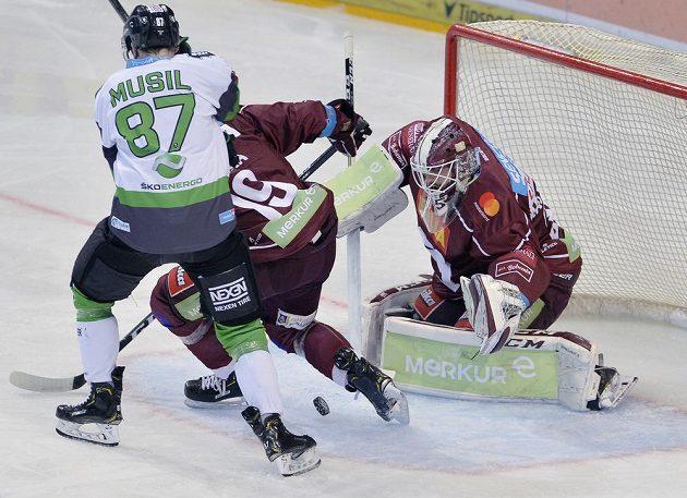 Mladoboleslavský hokejista Pavel Musil se snaží prosadit před brankou Sparty. Tu hájil Matěj Machovský, bránit pomáhá sparťan Tomáš Pavelka.