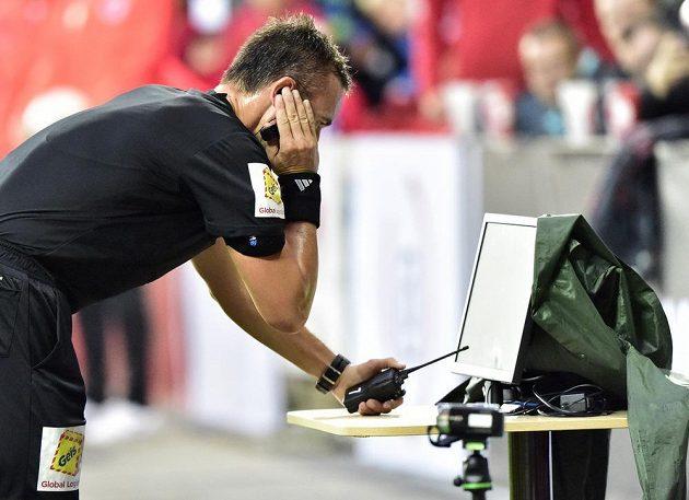 Rozhodčí Petr Ardeleánu kontroluje u videa spornou situaci, po které nařídil penaltu pro Slavii.
