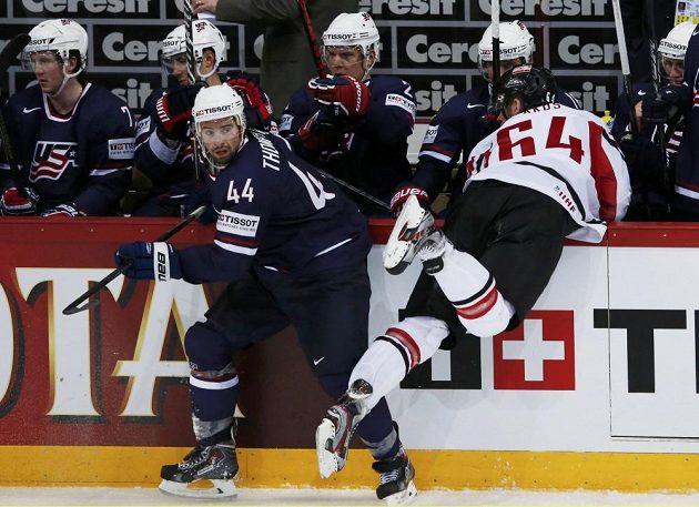 Rakouský hráč Lakos letí na americkou střídačku po srážce s Thompsonem.