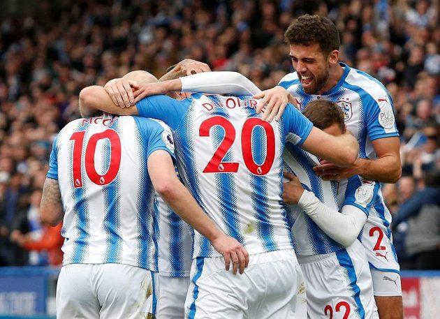 Fotbalisté týmu Huddersfield Town v euforii. Laurent Depoitre slaví svůj druhý gól v síti favorizovaného Manchesteru United se spoluhráči , kterými jsou Aaron Mooy, Tommy Smith. Huddersfield vyhrál 2:1.