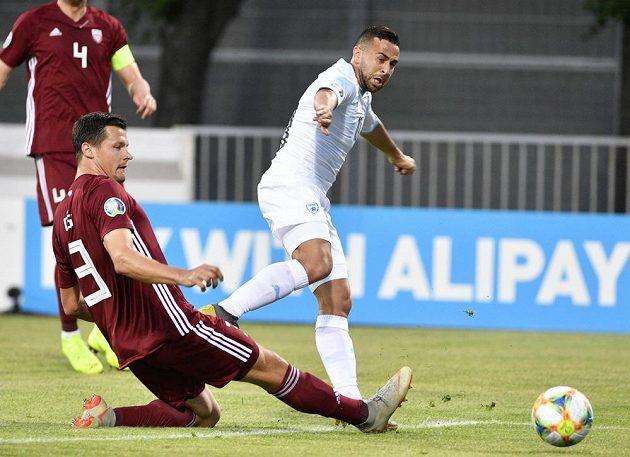Lotyšský fotbalový reprezentant Marcis Oss se snaží zastavit míč, který odehrál Izraelec Dia Seba v utkání kvalifikace o postup na EURO 2020.