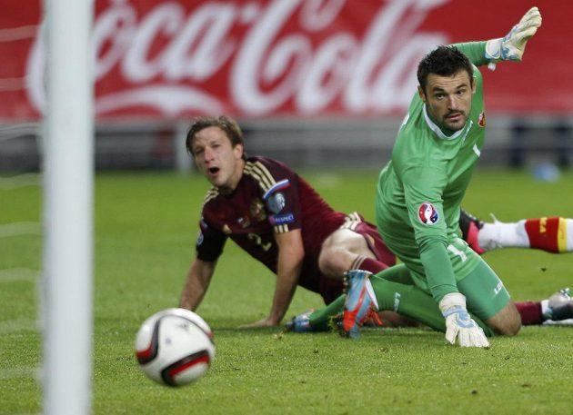 Černohorský gólman Milan Mijatovič sleduje míč, který míří do jeho branky po střele Rusa Olega Kuzmina (vlevo).