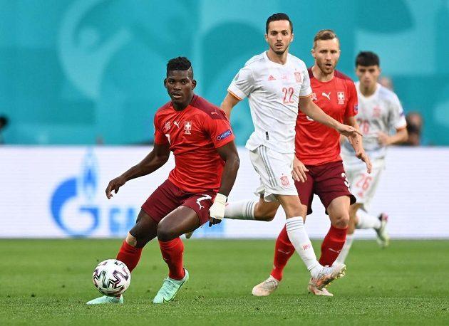 Švýcarský fotbalista Breel Embolo v akci během čtvrtfinále EURO. Jeho počínání sleduje Španěl Pablo Sarabia.