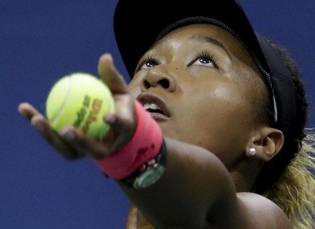Naomi Ósakaová si nadhazuje míček při podání.