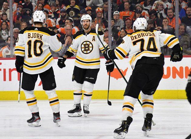 Hokejový útočník Bostonu David Krejčí (46) se spoluhráči gól vstřelený na ledě Philadelphie.
