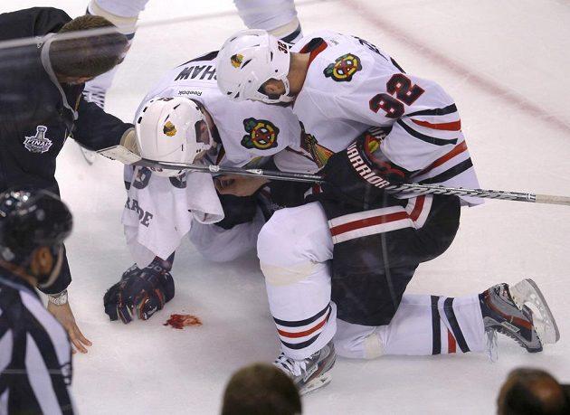 Obránce Chicaga Michal Rozsíval (vpravo) pomáhá spoluhráči Shawovi, jenž dostal pukem do obličeje.