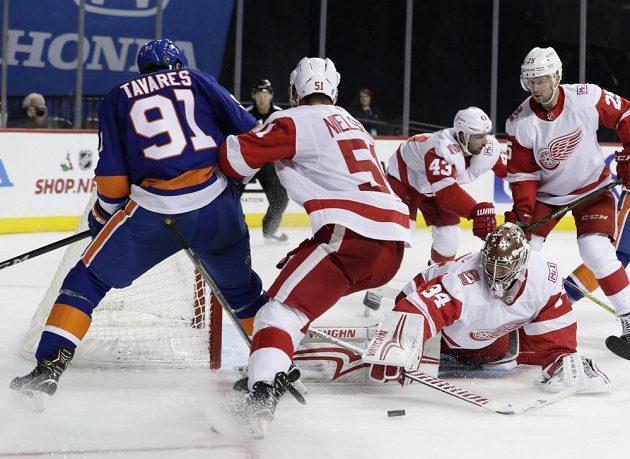 Petr Mrázek (34) zasahuje po ataku Johna Tavarese (91) z NY Islanders.