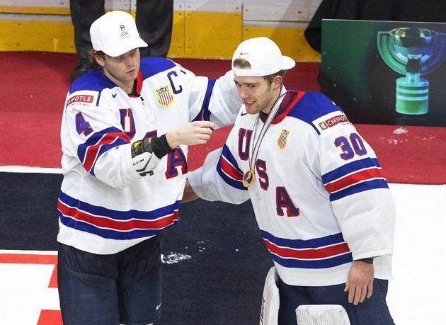 Euforie v podání mladých hokejistů USA po výhře ve finále na MS dvacítek. Cam York (4) dává zlatou medaili brankáři Spenceru Knightovi (30).