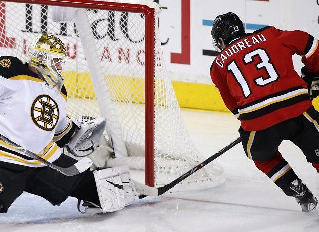 Americký forvard Johnny Gaudreau (13) z Calgary doráží na finského gólmana Tuukku Raska (40) z Bostonu.