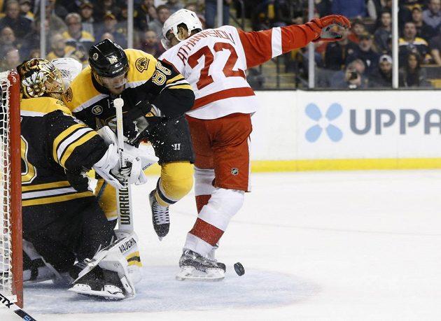 Útočník Bostonu David Pastrňák se snaží zastavit v utkání NHL útočícího Andrease Athanasiou a pomáhá tak brankáři Bruins.