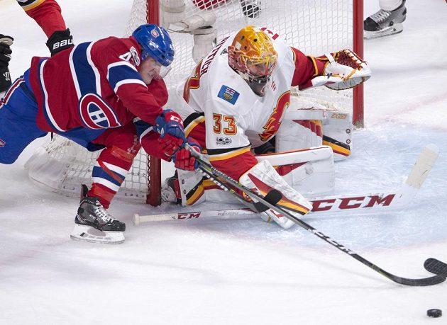 Útočník Montrealu Canadiens Daniel Carr se natahuje za pukem v utkání NHL proti Calgary, stejný záměr má i gólman Plamenů David Rittich.